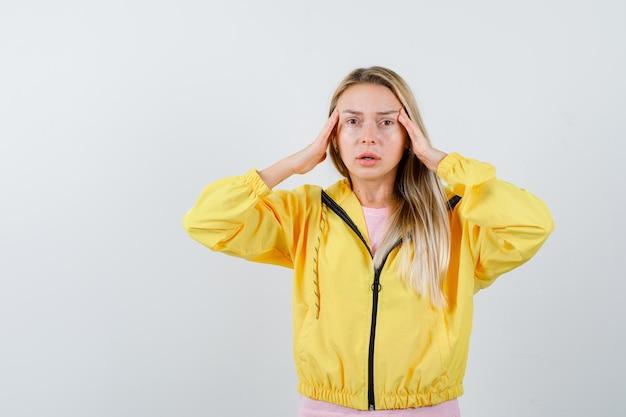 Ragazza bionda che si strofina le tempie con una giacca gialla e sembra sconvolta