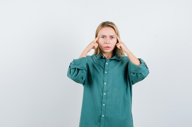 Blonde girl rubbing temples in green blouse and looking serious