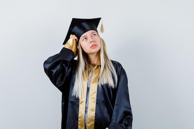 ブロンドの女の子が頭をかいて、卒業式のガウンとキャップで何かを考えて、物思いにふけるように見えます。