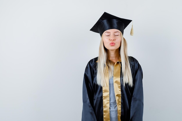 Blonde girl sending kisses in graduation gown and cap and looking cute.