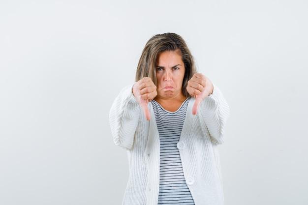스트라이프 티셔츠, 흰색 카디건 및 진 바지에 이중 엄지 손가락을 보여주는 금발 소녀와 불쾌한 표정. 전면보기.