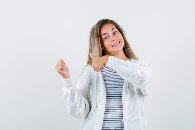 스트라이프 티셔츠, 흰색 카디건 및 진 바지에 두 엄지 손가락을 보여주는 금발 소녀와 행복을 찾고 있습니다. 전면보기.