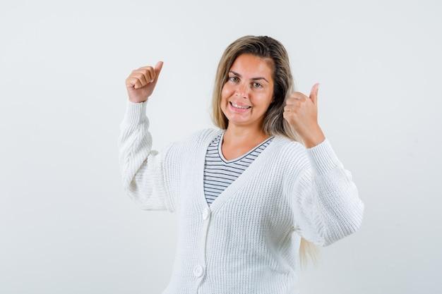 Ragazza bionda che mostra i doppi pollici in su in maglietta a righe, cardigan bianco e pantaloni jeans e sembra allegro, vista frontale.