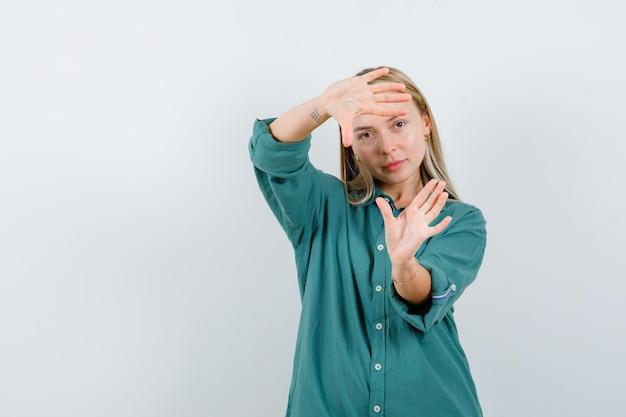 Ragazza bionda che mostra gesto di cornice in camicetta verde e sembra felice.