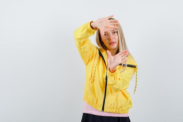 Ragazza bionda che mostra il gesto del telaio in maglietta rosa e giacca gialla e sembra carina.