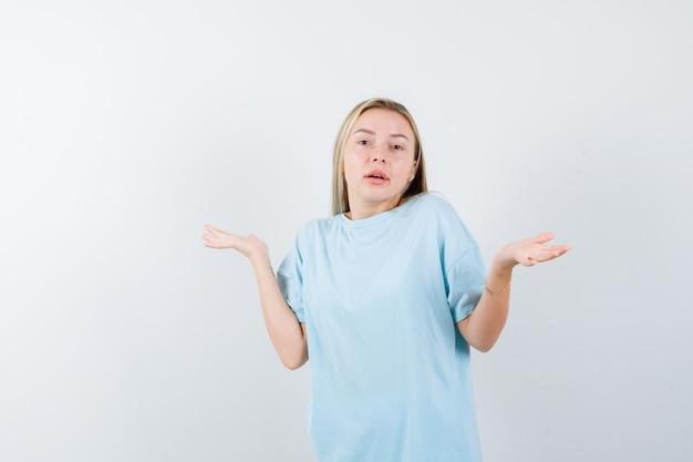 青いtシャツで無力なジェスチャーを示し、困惑しているように見えるブロンドの女の子、正面図。