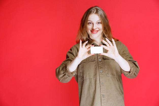 Блондинка показывает свою визитную карточку и сети.