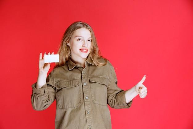 Блондинка показывает свою визитную карточку и положительный знак рукой.