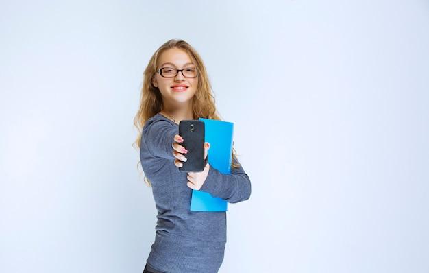 Ragazza bionda che mostra le sue immagini sul nuovo smartphone.