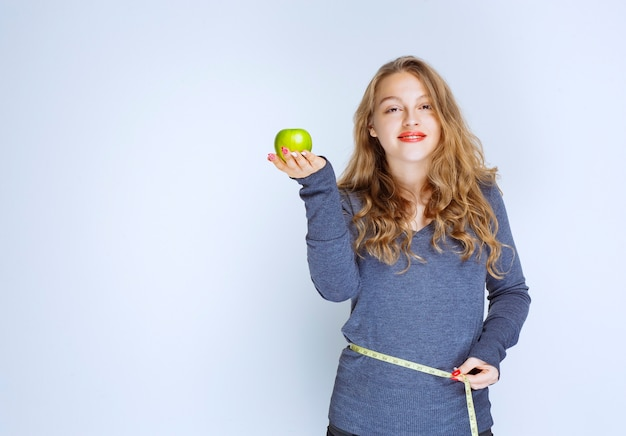Blonde girl showing her waist size while holding a green apple.