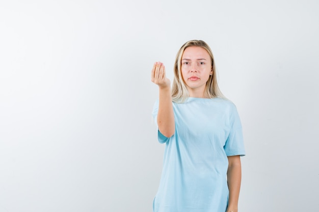 Ragazza bionda che mostra gesto italiano in maglietta blu e che sembra seria, vista frontale.