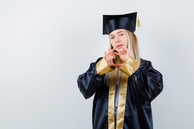 Ragazza bionda che mostra gesto d'amore con le mani in abito da laurea e berretto e sembra carina