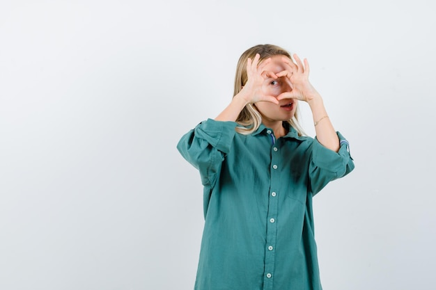 Blonde girl showing love gesture with hands in green blouse and looking enchanting
