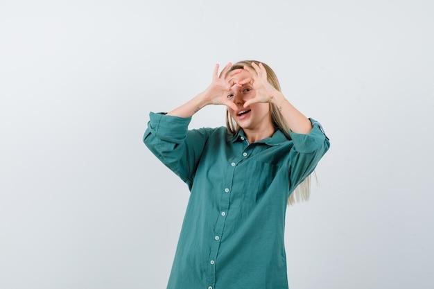 Ragazza bionda che mostra gesto d'amore con le mani in camicetta verde e sembra carina