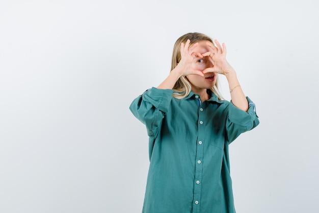 緑のブラウスで手で愛のジェスチャーを示し、魅惑的に見えるブロンドの女の子