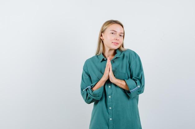 Ragazza bionda che mostra gesto di namaste in camicetta verde e sembra ottimista