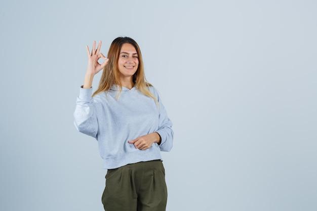 オリーブグリーンブルーのスウェットシャツとパンツでokサインを示し、輝く、正面図を探しているブロンドの女の子。