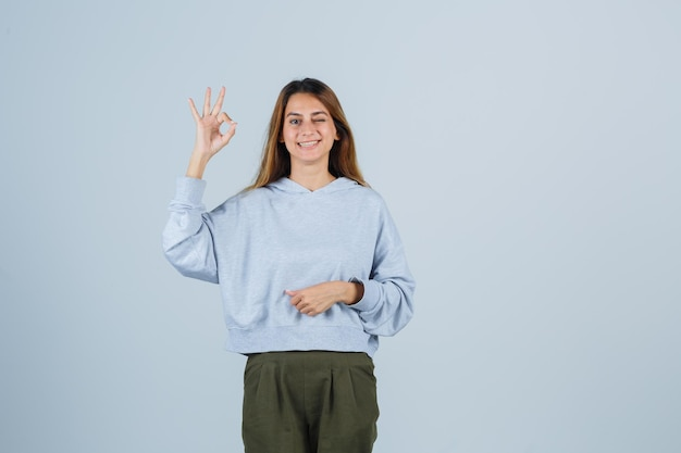 Blonde girl showing ok sign in olive green blue sweatshirt and pants and looking radiant , front view.