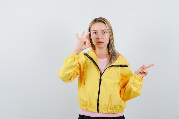 Блондинка показывает знак ок, указывает вправо в розовой футболке и желтой куртке и выглядит серьезно.