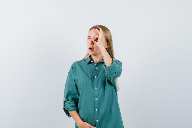 Блондинка показывает знак ок, держа руку на животе в зеленой блузке и выглядит довольно.