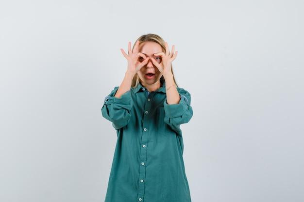 녹색 블라우스에 눈에 확인 표시를 보이고 즐겁게 보이는 금발 소녀