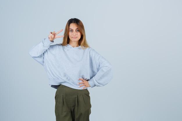 금발 소녀는 평화 제스처를 보여주고 올리브 녹색 파란색 운동복과 바지를 입고 허리에 손을 잡고 빛나는 앞모습을 보고 있습니다.