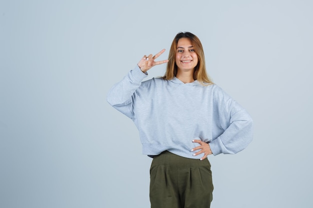 Blonde girl showing peace gesture and holding hand on waist in olive green blue sweatshirt and pants and looking happy , front view.