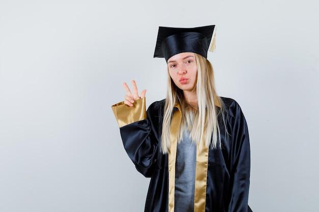 卒業式のガウンとキャップで平和のジェスチャーを示し、かわいく見えるブロンドの女の子