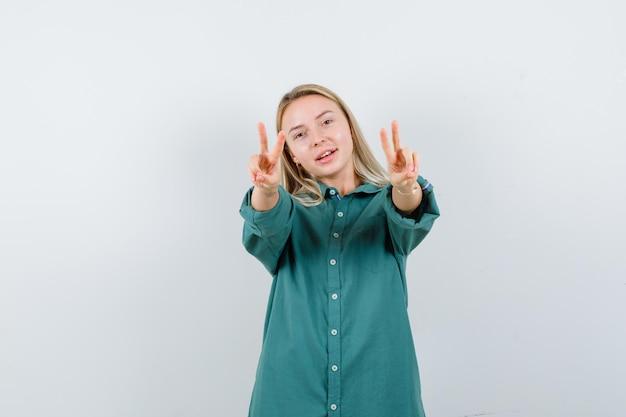 Ragazza bionda che mostra gesti di pace in camicetta verde e sembra felice