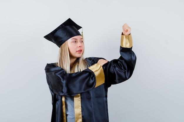 Ragazza bionda che mostra gesto di potere in abito e berretto da laurea e sembra sicura