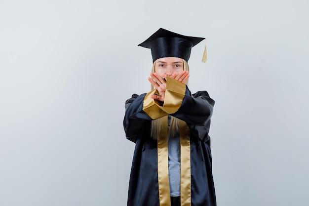 Ragazza bionda che mostra restrizione o gesto x in abito e berretto da laurea e sembra seria