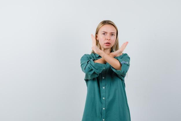 Ragazza bionda che mostra restrizione o gesto x in camicetta verde e sembra seria.