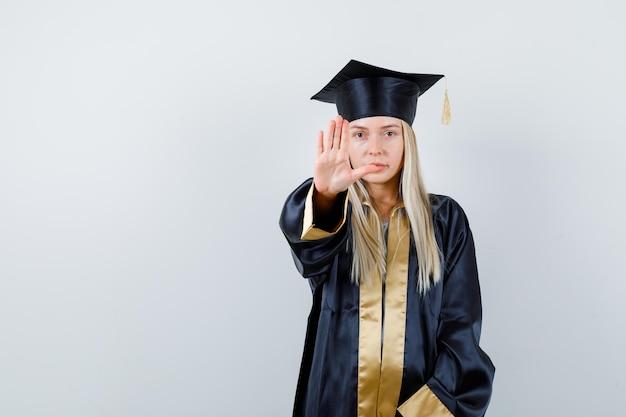 Блондинка показывает знак остановки в выпускном платье и кепке и выглядит серьезно.