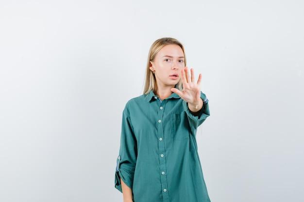 Блондинка показывает знак остановки в зеленой блузке и выглядит серьезно.