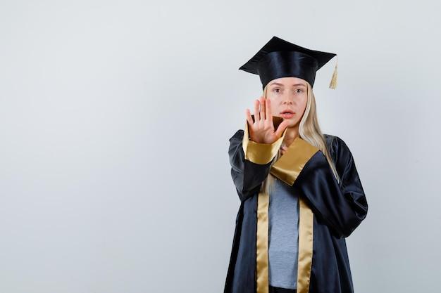 Ragazza bionda che mostra il segnale di stop, appoggiando la mano sul petto in abito da laurea e berretto e sembrando seria.