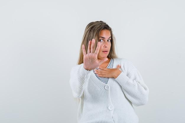 Блондинка показывает знак остановки, держа руку на груди в полосатой футболке, белом кардигане и джинсовых штанах и выглядит серьезным, вид спереди.