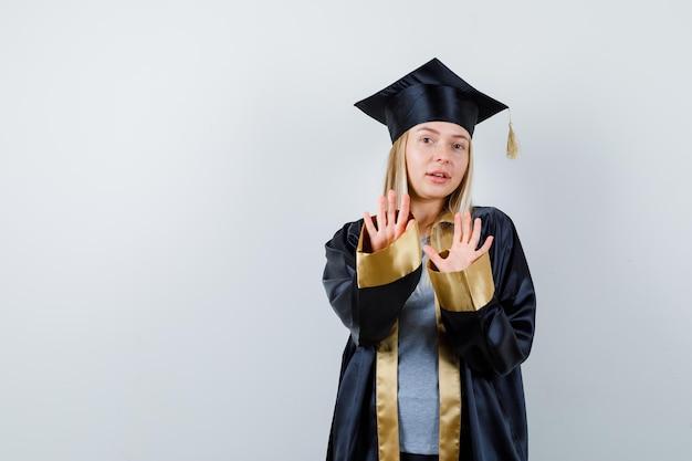卒業式のガウンとキャップで一時停止の標識を示し、真剣に見えるブロンドの女の子。