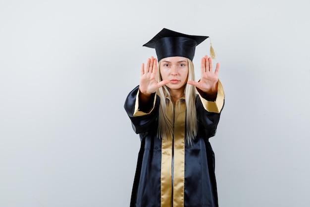 졸업 가운과 모자에 정지 신호를 표시 하 고 심각한 찾고 금발 소녀.