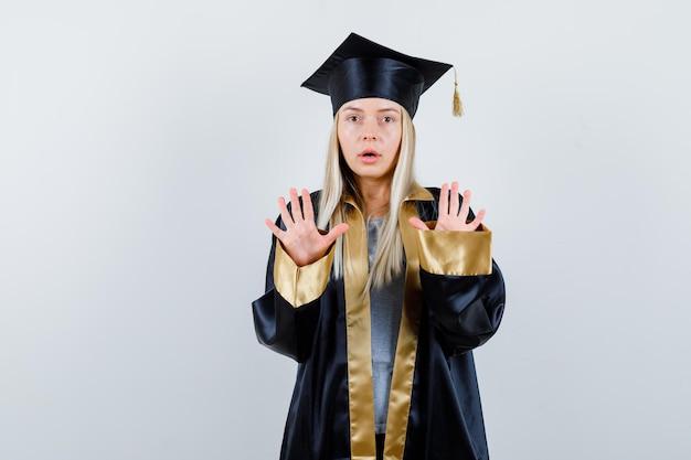 Блондинка показывает знаки остановки в выпускном платье и кепке и выглядит удивленным.