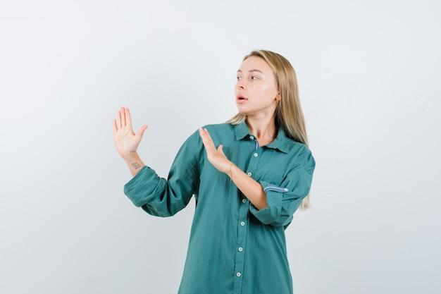 Блондинка показывает знаки остановки в зеленой блузке и выглядит серьезно.