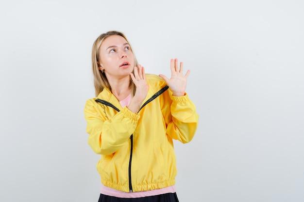 ピンクのtシャツと黄色のジャケットで一時停止の標識を示し、驚いて見えるブロンドの女の子