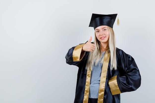 卒業式のガウンとキャップで腰に手を握り、幸せそうに見えながら親指を上に表示するブロンドの女の子
