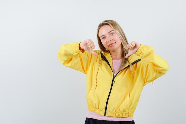 Блондинка показывает палец вниз обеими руками в розовой футболке и желтой куртке и выглядит счастливой