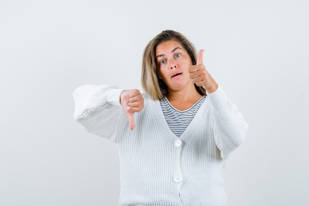ストライプのtシャツ、白いカーディガン、ジーンズのズボンで親指を上下に見せて、真剣に正面から見ているブロンドの女の子。