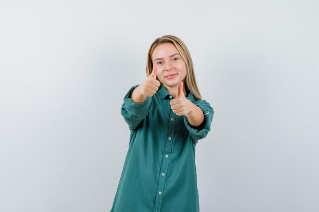 Блондинка показывает палец вверх обеими руками в зеленой блузке и выглядит впечатленным