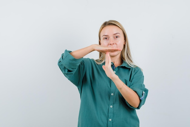Blonde girl showing time-break gesture in green blouse and looking serious