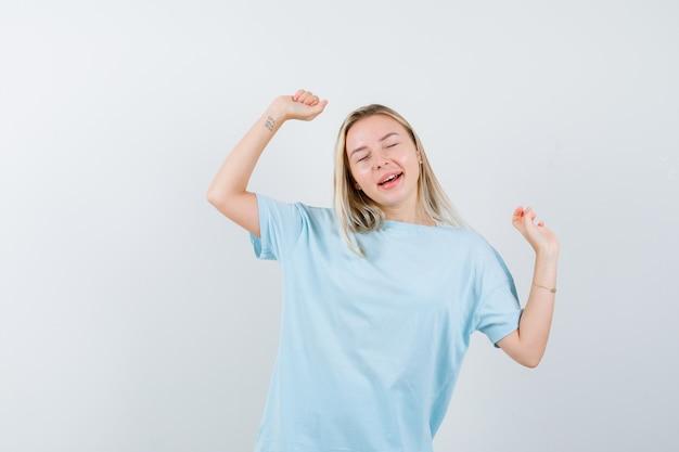 青いtシャツで勝者のジェスチャーを示し、陽気に見えるブロンドの女の子、正面図。