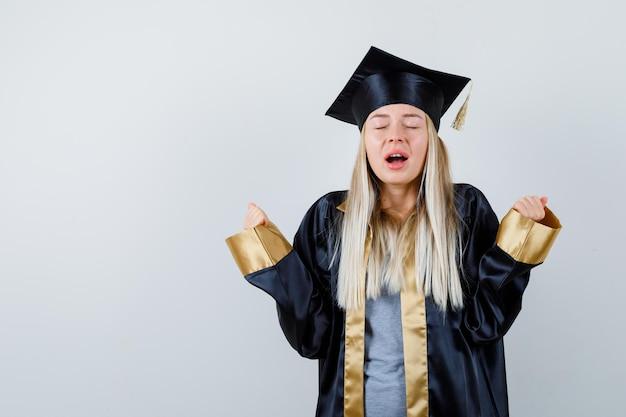 졸업 가운과 모자에 우승자 제스처를 보여주고 쾌활한 찾고 금발 소녀