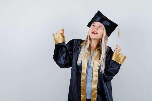 卒業式のガウンとキャップで勝者のジェスチャーを示し、幸せそうに見えるブロンドの女の子。