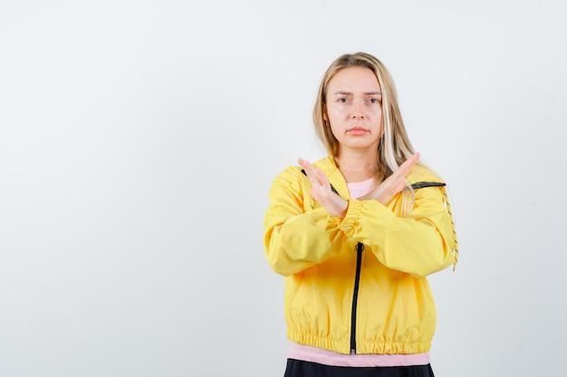 Ragazza bionda che mostra x o gesto di restrizione in maglietta rosa e giacca gialla e sembra seria